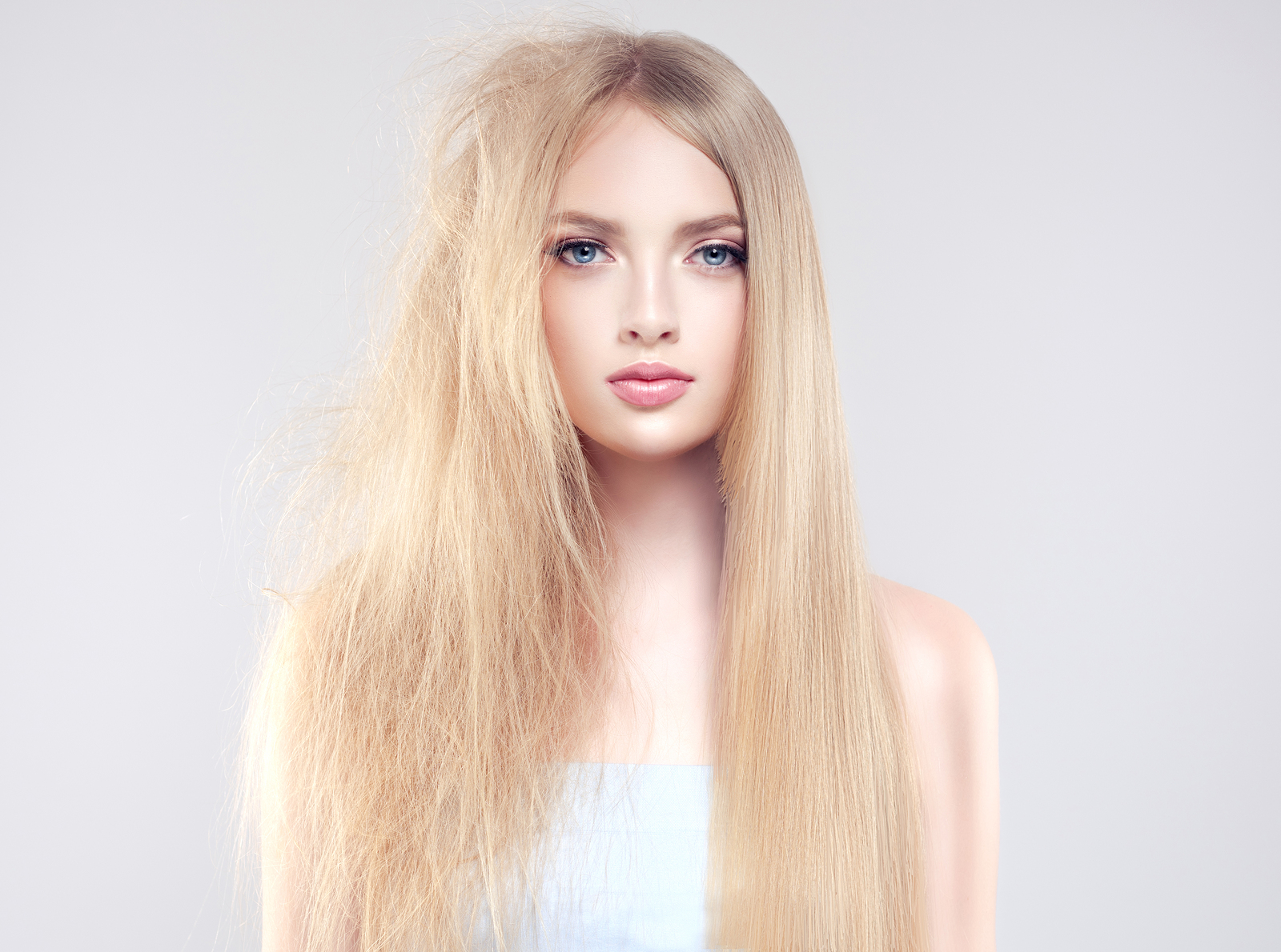 Straightening , smoothing and treatment of the hair . Model girl a half a head straight and smooth hair .The other half of head with tangled unbrushed hair. Care and hair products