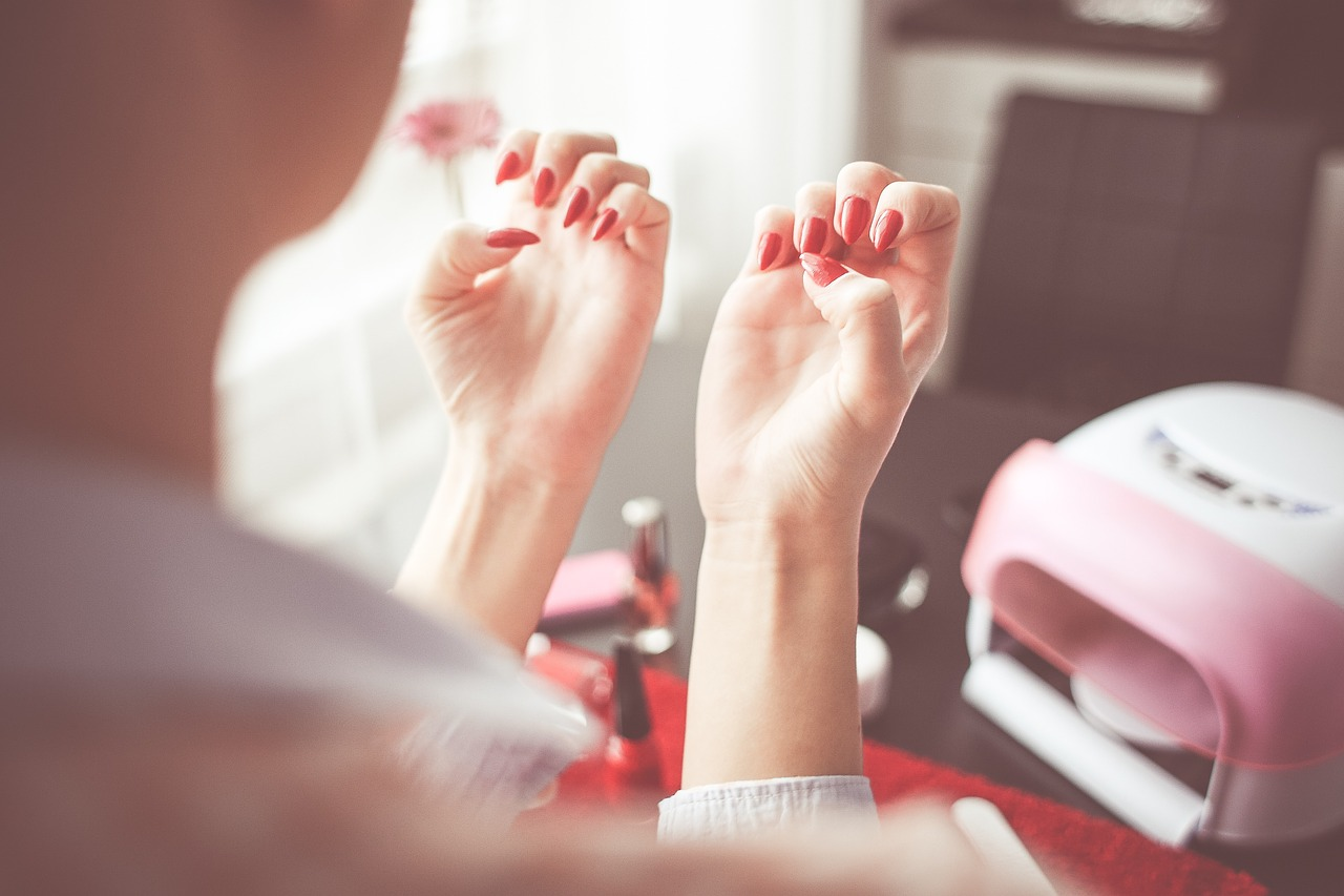 woman looking at her beautifully painted red finger nails